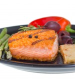 Grilled salmon steak on plate served with olives, asparagus and bell pepper isolated on white background.