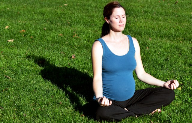 Pregnant woman yoga exercise during pregnancy outdoor at the park. Concept photo of women healthy life style and health care. copy space